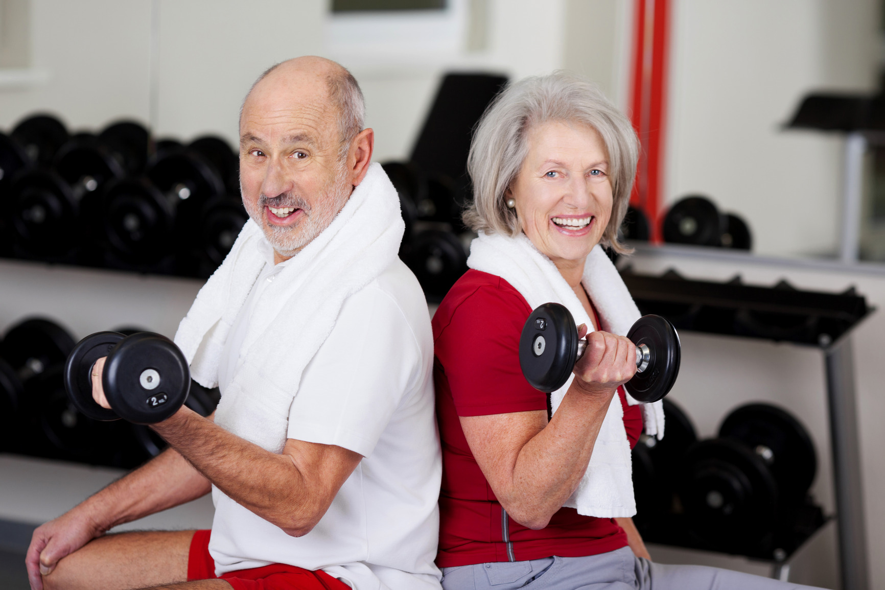 Senior Couple Lifting Dumbbells While Sitting In Gym